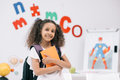 African american schoolgirl with backpack holding textbook and smiling at camera in classroom Royalty Free Stock Photo