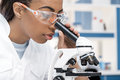 African american scientist in lab coat working with microscope in chemical lab Royalty Free Stock Photo