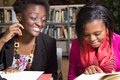 African american students playful in the library young female at Royalty Free Stock Image
