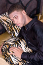 African american vampire waking up his gothic bed night out town model has very light charcoal make up to enhance dark evil look Stock Photo