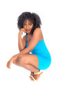African american woman crouching a young pretty in a blue dress and curly black hair on the floor isolated for white background Stock Photos