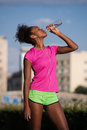 stock image of  African american woman drinking water after jogging