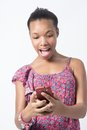 African american woman excited over chat message black female surprised while chatting on her phone Stock Image