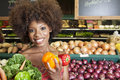 African american woman holding bell peppers and vegetables at supermarket women Stock Photo