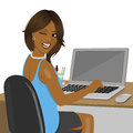 African american woman looking over shoulder sitting in office with laptop winking Royalty Free Stock Photo