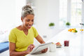 African american woman using digital tablet at home in kitchen looking screen smiling Stock Image