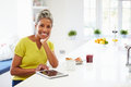 African american woman using digital tablet at home looking to camera smiling Royalty Free Stock Photography