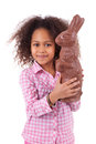 African Asian girl holding a giant chocolate rabbit Royalty Free Stock Images