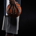 African basketball player holding ball cropped image of a young man against black background mid section image of Royalty Free Stock Photo