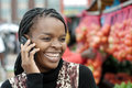 African or black american woman calling on landline telephone payphone in alexandra township market south africa Stock Image