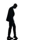 African black man standing looking down silhouette one in studio on white background Stock Photos