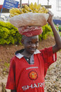African boy selling bananas with manchester united tricot sells from basket on the head to travellers in uganda Royalty Free Stock Image
