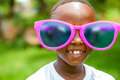 African boy wearing fun extra large sun glasses close up face shot portrait of cute huge over sized outdoors Royalty Free Stock Photos