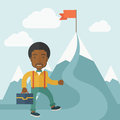 African businessman holding his bag an will climb up to top of the mountain to achieve success by the red flag willingness Royalty Free Stock Images