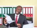 African businessman at office is happy about good laughing with tie and dark suit his the letter with news Royalty Free Stock Photo
