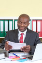 African businessman reading a message with tie and dark suit at his office letter Royalty Free Stock Photos