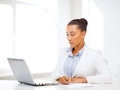 African businesswoman writing something business and technology concept with laptop in notebook Stock Image
