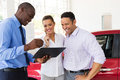 African car dealer couple explaining sales contract to buying a Royalty Free Stock Photography