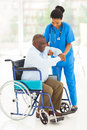 African caregiver helping senior friendly men getting up from wheelchair Stock Images
