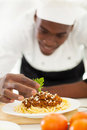 African chef garnishing spaghetti in kitchen Stock Photo