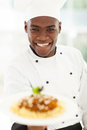 African chef presenting close up portrait of in hotel kitchen pasta Stock Photography