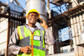 African chemical worker oil and talking on cell phone Stock Photos