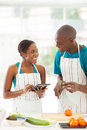 African couple recipe smiling searching for a using tablet computer Royalty Free Stock Photography