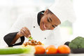 African female chef beautiful garnishing spaghetti dish Stock Image