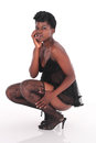 African female in underwear crouching black looking at subject with her hand by her mouth Royalty Free Stock Photo