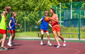 African girl holds ball and teens play basketball Royalty Free Stock Photo