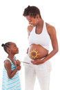 African girl painting on her mother s belly little american isolated white background people Stock Photography