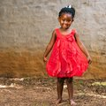 African girl showing red dress full length portrait of cute outdoors Royalty Free Stock Photos