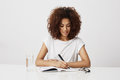 African girl thinking writing in notebook smiling over white background. Copy space. Royalty Free Stock Photo