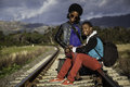 African guy and girl waiting for train on the tracks Stock Photos