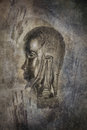 African head sculpture carved idol against a grunge textured background of primitive ghostly cave painting hand prints Royalty Free Stock Photography