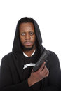 African hooligan or gangster with a gun wearing black hooded top in his hand looking grimly at the camera in threatening Royalty Free Stock Photo