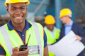 African industrial worker happy american with walkie talkie on site with colleagues Stock Photos