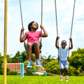 African kids having fun swinging in park action portrait of out of focus houses background Royalty Free Stock Image