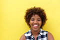 African lady laughing against yellow wall Royalty Free Stock Photo