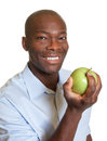 African man eating an apple laughing from africa loves fresh green apples Stock Photos