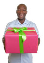 African man hands out his christmas gift attractive has a colorful in hand on a white background Royalty Free Stock Photography