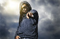 African man in hoodie pointing at camera with stormy sky background and light Royalty Free Stock Photos