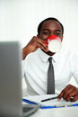 African man sitting at his workplace and drinking coffee in office Royalty Free Stock Photos