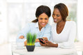 African mother daughter phone beautiful and using smart at home Royalty Free Stock Photography