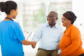 African nurse greeting senior couple friendly female in hospital Stock Photos