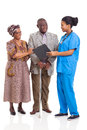 African nurse senior couple young female talking to isolated on white background Royalty Free Stock Photo