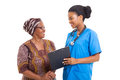 African nurse senior woman beautiful young helping women with medical form Royalty Free Stock Images