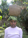 African peasant girl  carrying reed  basket on  head. Royalty Free Stock Photo