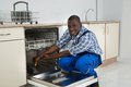 African Repairman Repairing Dishwasher Royalty Free Stock Photo