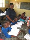 African school teacher with pupils in classrom